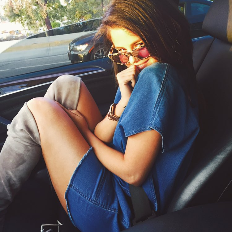 10 selena gomez - denim dress with thigh-high boots and printed sunglasses