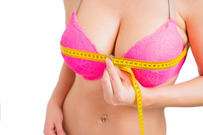 how to measure bra size - girl measuring the bust size using a measuring tape
