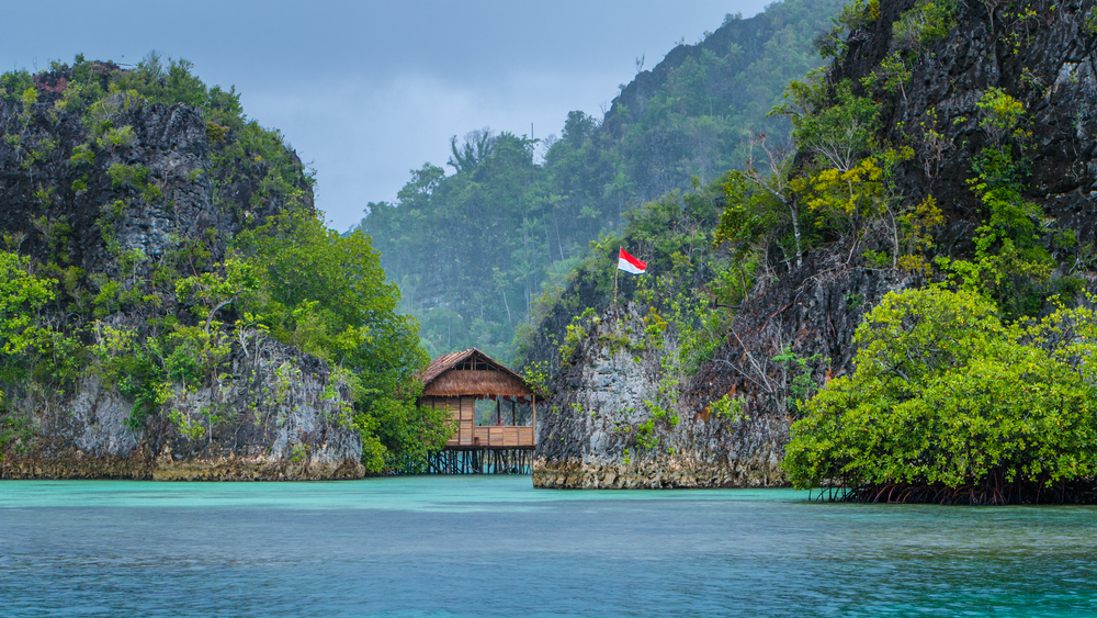 Bamboo Hut between some Rocks under Rain in Bay  Painemo Islands  Raja Ampat  West Papua  Indonesia