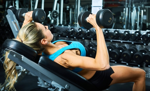woman doing bench press with dumbells in the gym strength training exercises for breast reduction