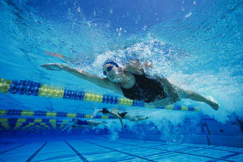 woman in black bathing suit swimming. home exercises for reducing breast size