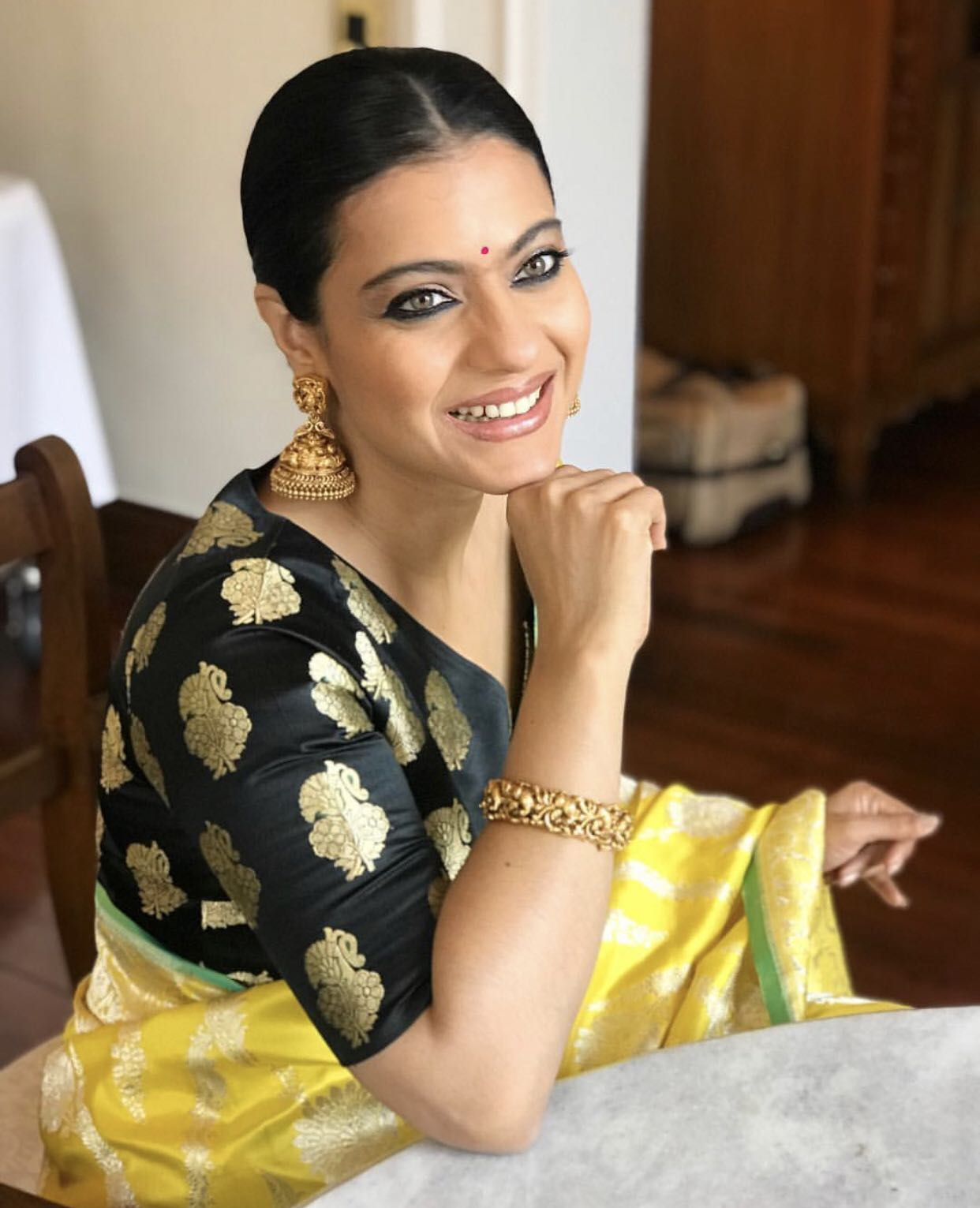 kajol makeup and hair smiling picture from radhika mehra instagram yellow saree bun