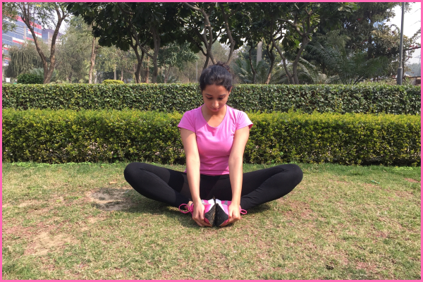 woman-sitting-on-ground-doing-butterfly-stretch