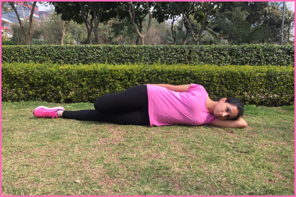 Woman-lying-on-ground-doing-side-stretch