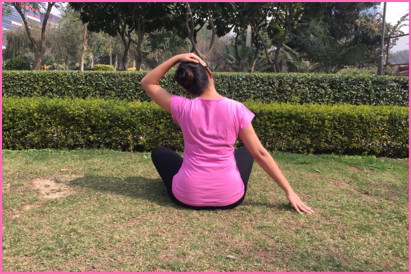 woman-sitting-on-ground-doing-neck-stretch