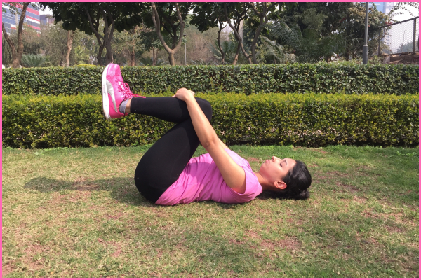 woman-lying-on-ground-doing-crunches-pose