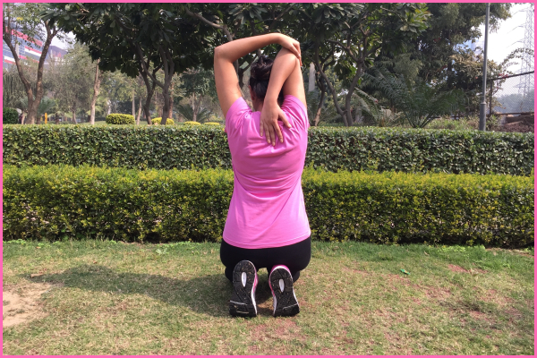 woman-sitting-on-ground-doing-triceps-stretch