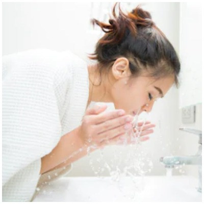 Girl washing her face with facewash