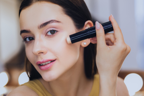 woman-using-a-concealer-stick