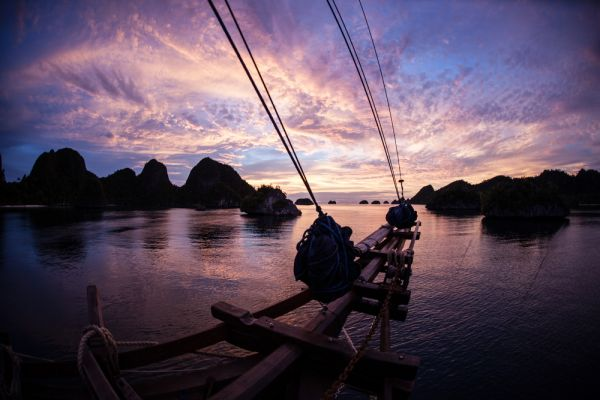 A gorgeous sunset silhouettes the bow of a ship as it lays at anchor in a remote lagoon surrounded by limestone islands in Raja Ampat  Indonesia