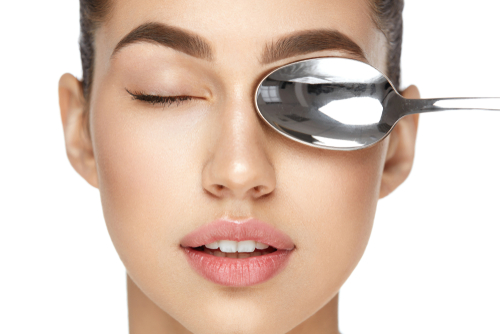 woman icing eyes with cold spoon get rid of puffy eyes