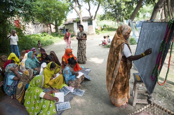women in village studying - importance of education for women