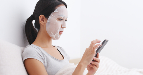 woman with a sheet mask on her bed looking at her smartphone