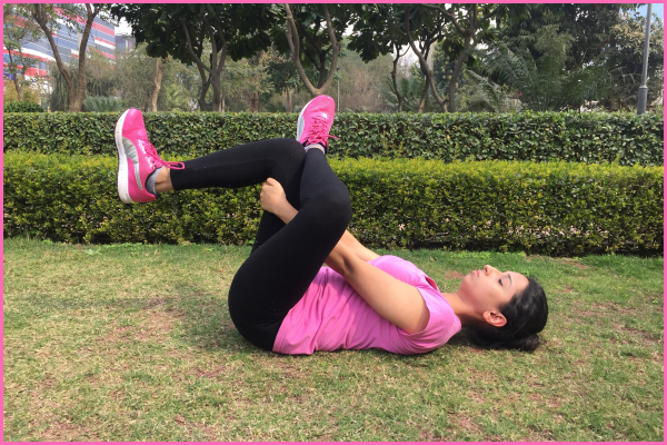 woman-lying-on-ground-doing-figure-four-stretch