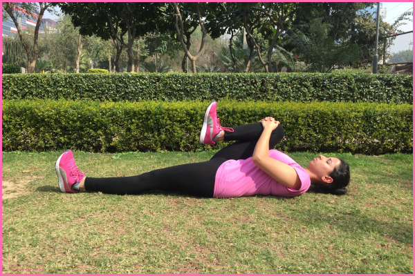 Woman-lying-on-ground-doing-one-knee-to-chest-stretch
