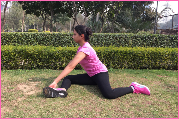 woman-sitting-on-ground-doing-right-angle-stretch