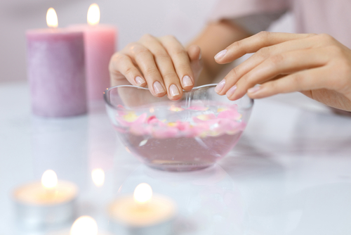 manicure dipping fingers into a bowl of hot water