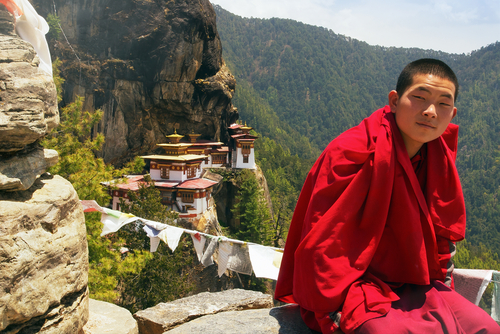 2 Buddhist monk seats with Taktsang Monastery  located on the cliff side of a mountain  or Taktshang Goemba