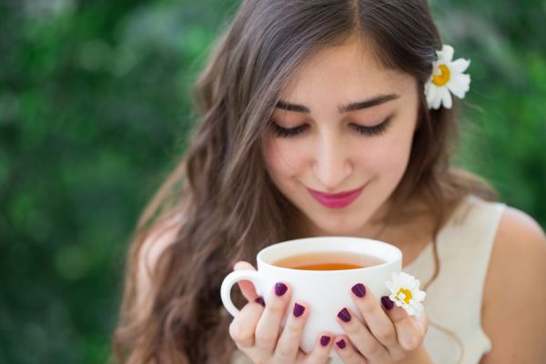 All You Need To Know About Chamomile Tea - girl with a cup of chamomile tea