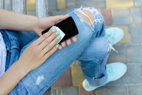 Woman wiping down her phone how smartphones cause bacteria