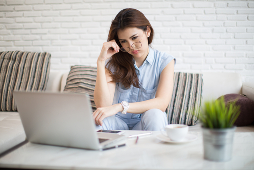 Woman sitting in one place looking worried and tired