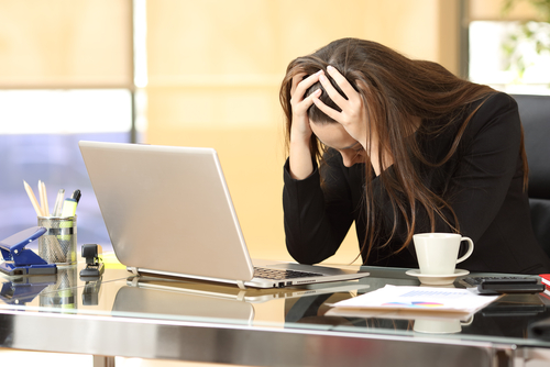 1-burnout-girl-holding-head-at-work