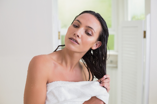 woman wiping hair with towel post shampooing