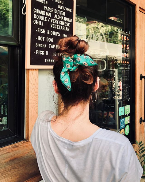 a women locking her high bun with a scarf