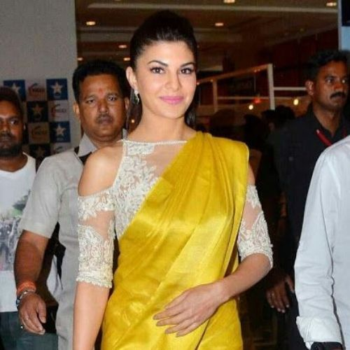 Jacqueline Fernandez in sheer cold shoulder high neck blouse