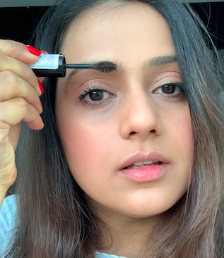 Applying eyebrow mascara