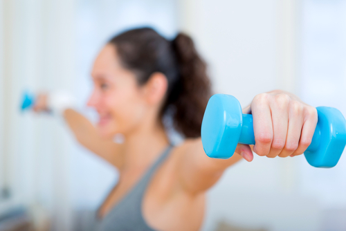 a women is doing Isometric shoulder exercises using a pair of dumbbells