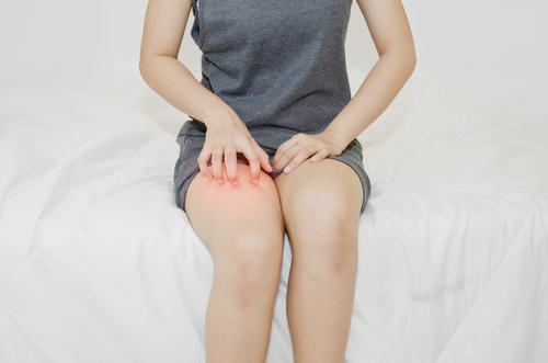 woman scratching her knee