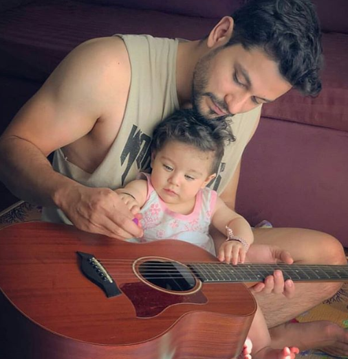 a daughter is playing guitar with her father