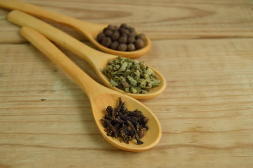 cloves and other herbs on a spoon