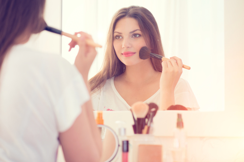 woman applying blush with a makeup brush
