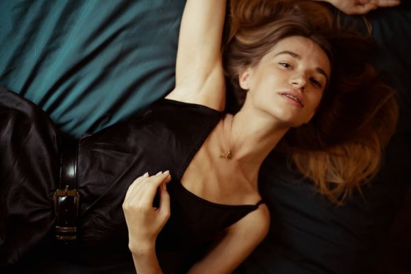 woman exposing her underarms while lying on the bed