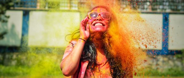 girl playing holi with colours